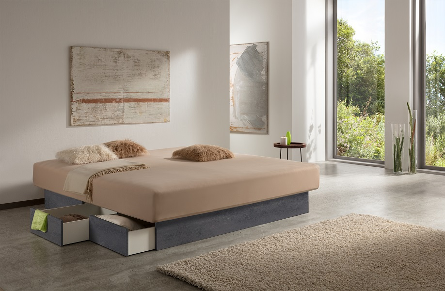 Aufnahme  von einem Wasserbett mit Schubladen, das im dunkelgrauen Schiefer-Look gehalten ist und zentral in einem hellen Raum steht. Rechts befinden sich eine Fensterwand und ein beiger Teppich. Einige Schubladen des Wasserbetts sind geöffnet.