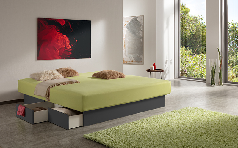 Foto eines Wasserbetts mit offenen Schubladen am anthraziten Bett-Sockel, inmitten eines modernen Schlafzimmers.