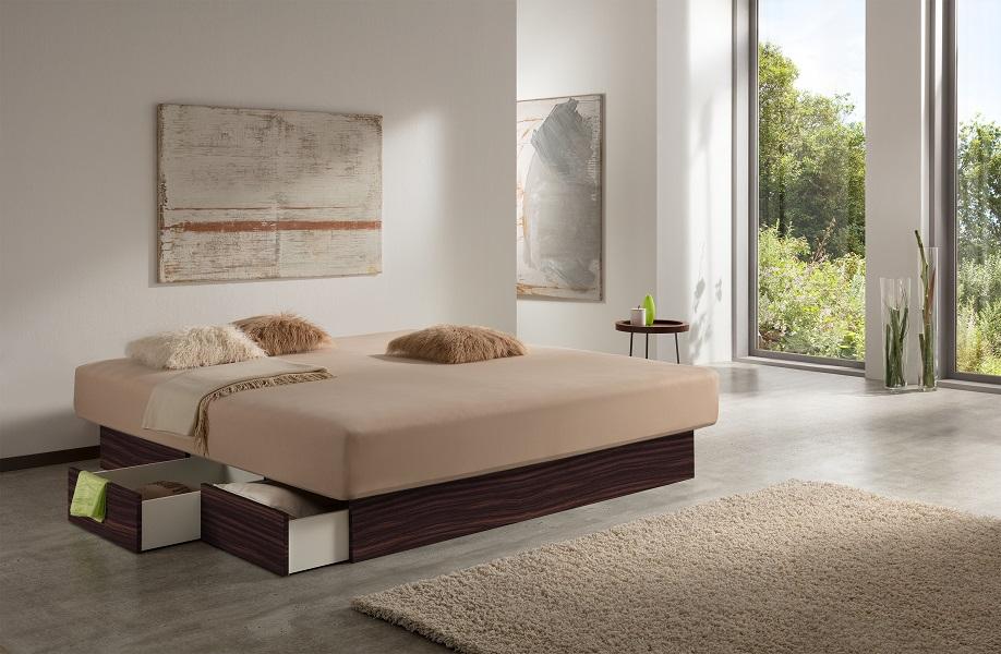 """Foto von einem Wasserbett mit Schubladen in einem hellen Raum zur Tageszeit. Das Wasserbett besitzt ein Schubladenpodest im Look """"Makassar"""", welcher an das begehrte Ebenholz erinnert."""