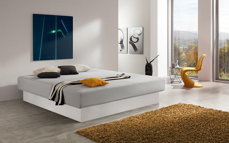 Foto eines Wasserbetts mit Sockel in Weiß, inmitten eines modernen Schlafzimmers