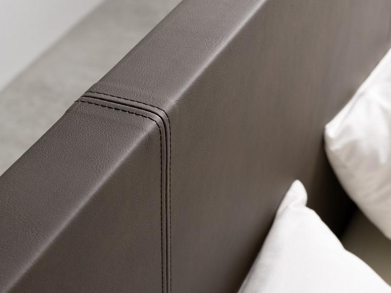 Nahaufnahme eines Kopfteils von einem Estrella Wasserbett. Das Kopfteil ist in einem brauen Leder-Design gehalten.