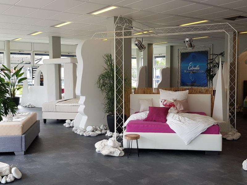 Innenaufnahme des Kallisto Wasserbett Studios in Dreieich bei Frankfurt am Main.  Rechts befindet sich ein Wasserbett mit weißer Verkleidung und purpur Bettzeug, während links Dekor wie Steine und große Topfpflanzen zu sehen sind