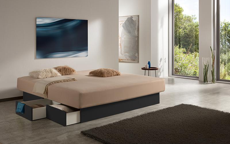 Foto eines Wasserbetts mit offenen Schubladen am schwarzen Bett-Sockel, inmitten eines modernen Schlafzimmers.