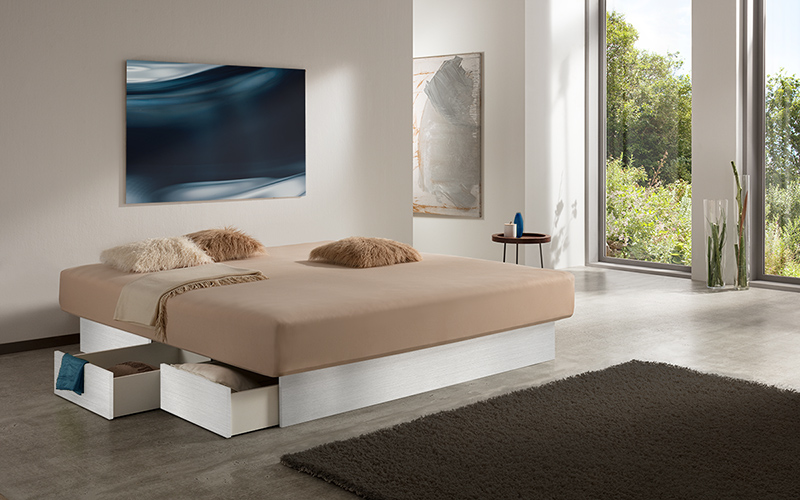 Foto eines Wasserbetts mit offenen Schubladen am Edelstahl-Bett-Sockel, inmitten eines modernen Schlafzimmers.