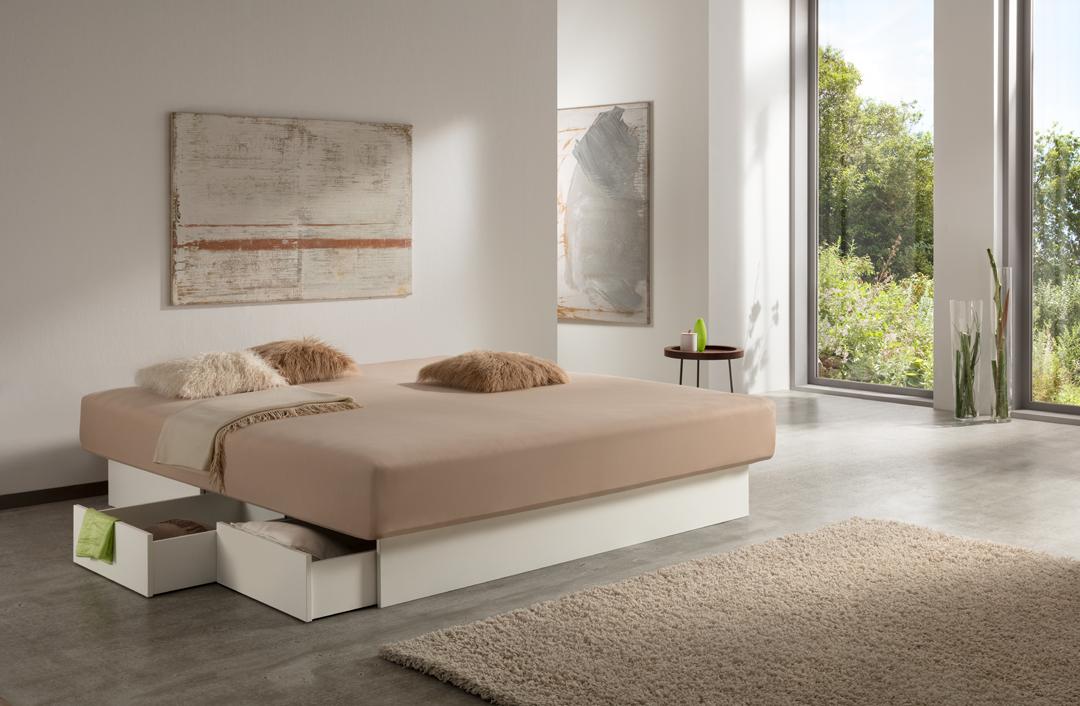 Wasserbett mit weißen Schubladen & einem beigen Spannbett-Tuch inmitten eines hellen Zimmers