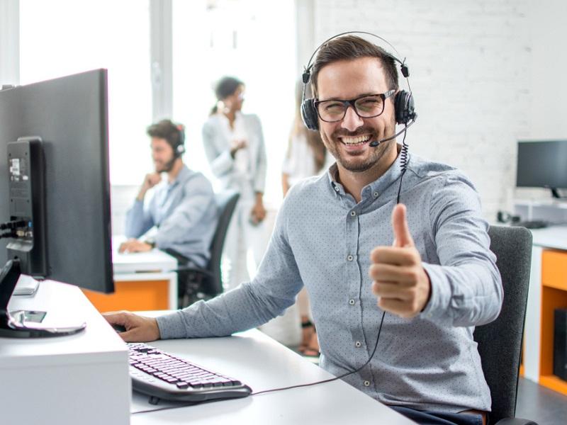 Mitarbeiter im Call-Center mit blauem Hemd und Headset, welcher den Daumen hochstreckt. Mitarbeiter im Call-Center mit graublauem Hemd und Headset. Das Foto steht sinnbildlich für die Beratungs-Hotline der Kallisto GmbH.