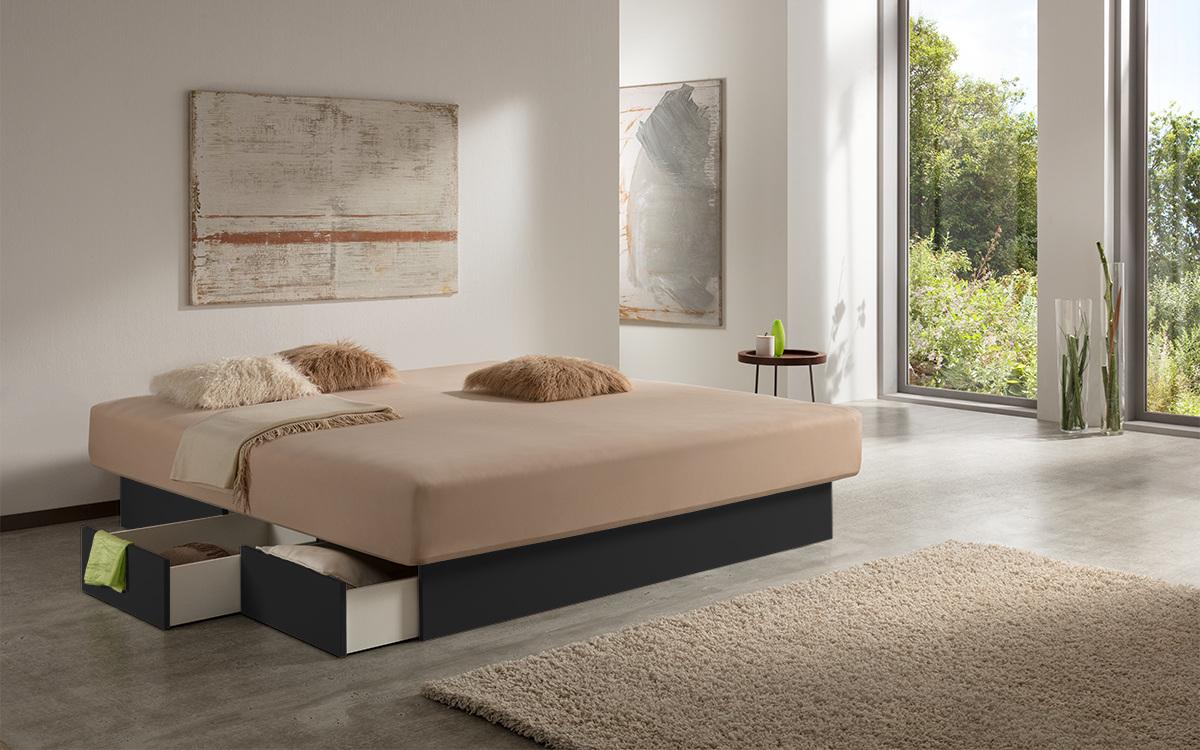 Wasserbett mit schwarzen Schubladen & einem beigen Spannbett-Tuch inmitten eines hellen Zimmers