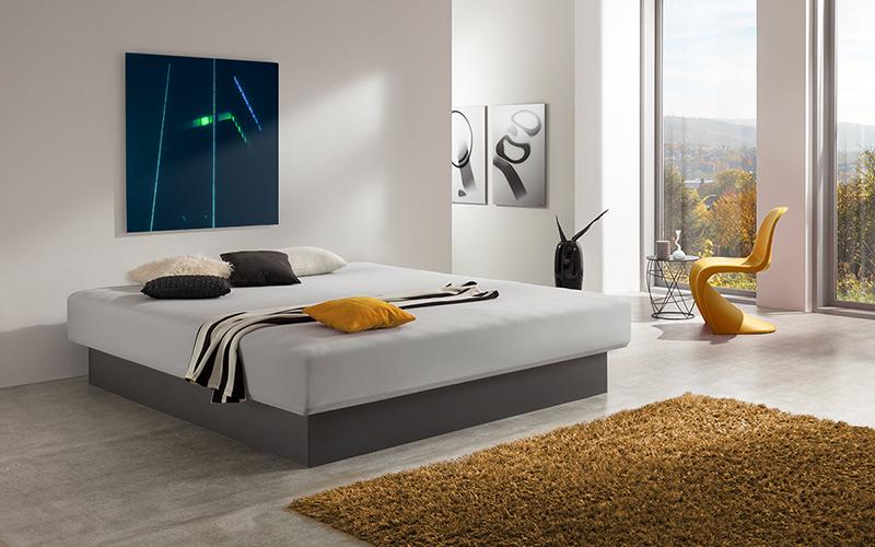 Foto eines Wasserbetts mit Sockel in Anthrazit, inmitten eines modernen Schlafzimmers
