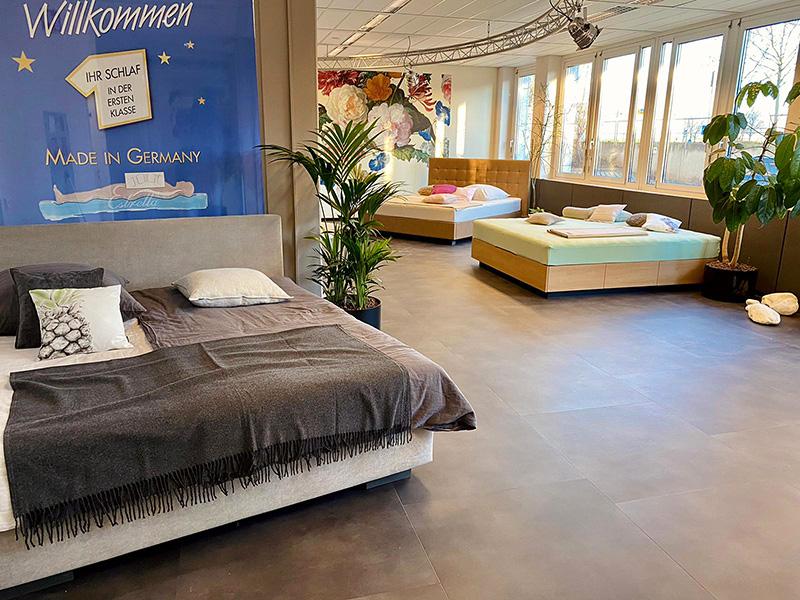 Innenaufnahme des Kallisto Wasserbett Studios in Stuttgart Leinfelden-Echterdingen. Zu sehen sind mehrere Wasserbetten in einem großen Raum mit Fenstern auf der rechten Seite und einem dunkelgrauen Fußboden.