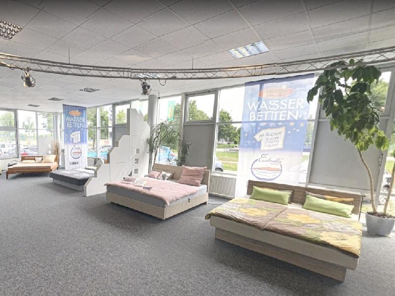Innenaufnahme des Kallisto Wasserbett Studios in Augsburg. Zu sehen sind mehrere Betten, die in einem hellgrauen Raum hinter einer Fensterwand stehen. Es ist Tag und der Raum ist mit Pflanzen dekoriert.