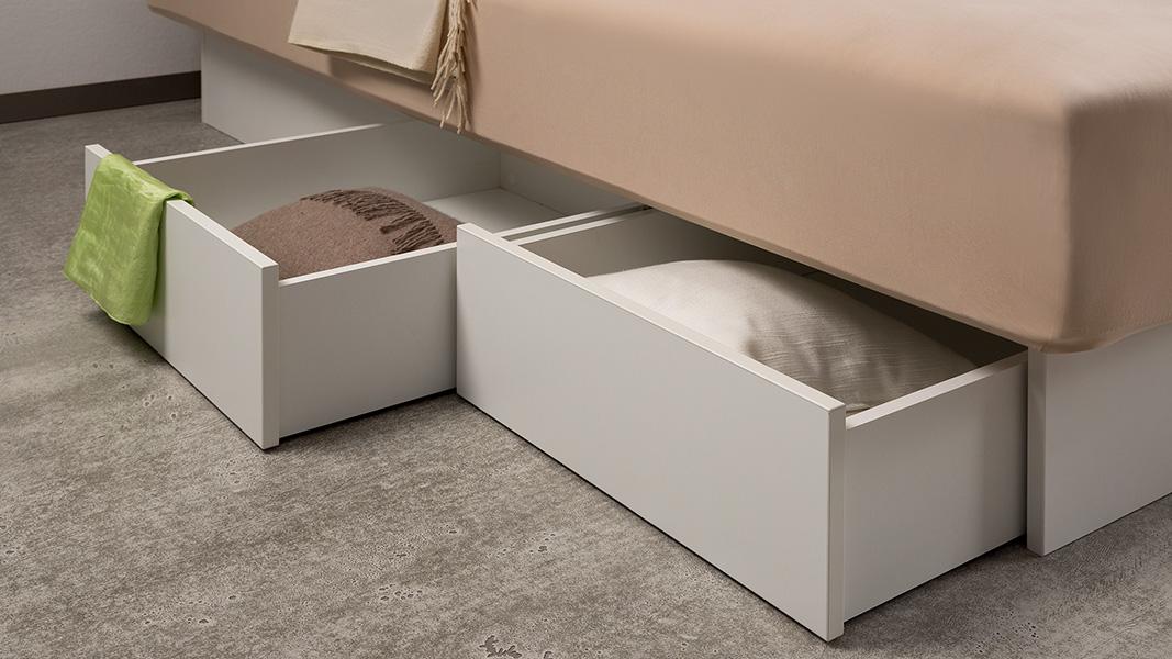 Nahaufnahme von zwei offenen Schubladen, die am Estrella Wasserbett mit Schubladen von Kallisto angebracht sind. Die Schubladen sind weiß, während der Spannbettbezug darüber einen beigen Farbton hat.