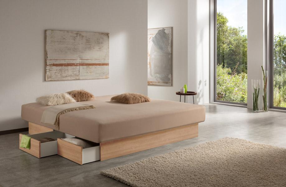 """Aufnahme eines Wasserbetts mit Schubladen, das einen beigen Bettbezug aufweist. Das Schubladenpodest des Wasserbetts ist im Design """"Eiche"""" gehalten."""