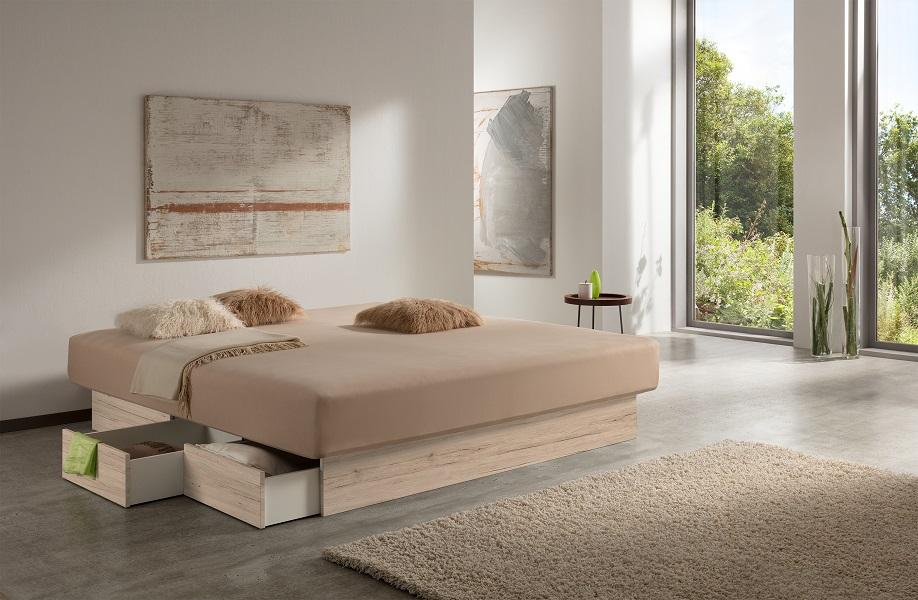 """Zu sehen ist das Estrella Wasserbett mit Schubladen, das sich in einem modern eingerichteten großen Zimmer befindet. Die Farbe des Schubladensockels des Wasserbetts nennt sich """"Sanremo Sand"""" und erinnert an helles hochwertiges Eichenholz."""