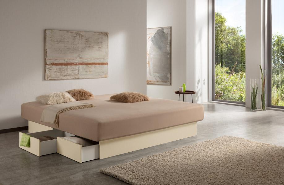Foto eines Wasserbetts mit Schubladen von Kallisto, das in einem einladenen Raum mit hellen Wänden und einem grauen Boden steht. Das Schubladenpodest ist in einer cremefarbenen Farbe gehalten. Einige der Schubladen am Wasserbett sind geöffnet.