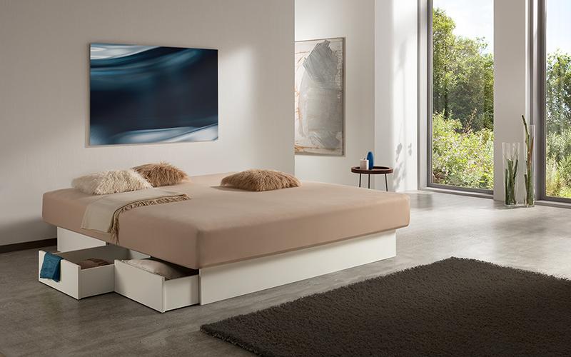 Foto eines Wasserbetts mit offenen Schubladen am weißen Bett-Sockel, inmitten eines modernen Schlafzimmers.