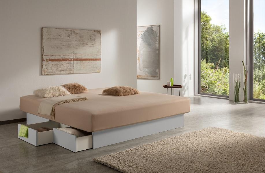 """Foto eines Wasserbetts mit Schubladen, das inmitten eines modernen Zimmers mit Fensterwand auf der rechten Seite steht. Einige der Schubladen des Wasserbetts sind geöffnet. Der Schubladensockel weist eine hellgraue Farbe im Stil """"Weißaluminium"""" auf."""